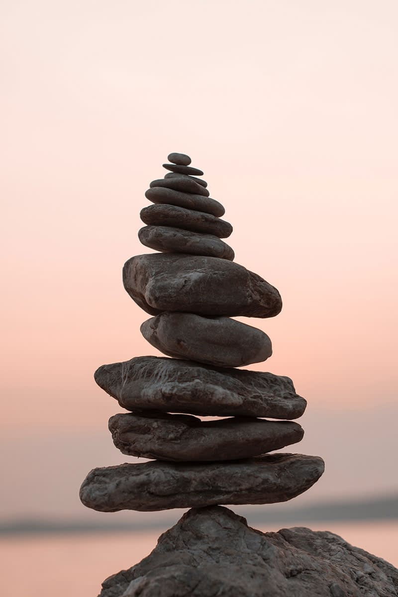 Vertically stacked and balanced rocks in front of light pink sunset